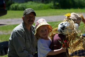 "Claire with her grandfather and her scarecrow named ""Claire""."